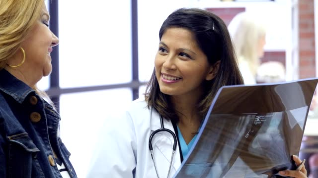 Cheerful mid adult Asian doctor talks with mature Hispanic female patient Cheerful female doctor smiles while giving good news to a mature Hispanic female patient. The doctor is holding an x-ray of the woman's foot. The patient smiles and nods her head. good news stock videos & royalty-free footage