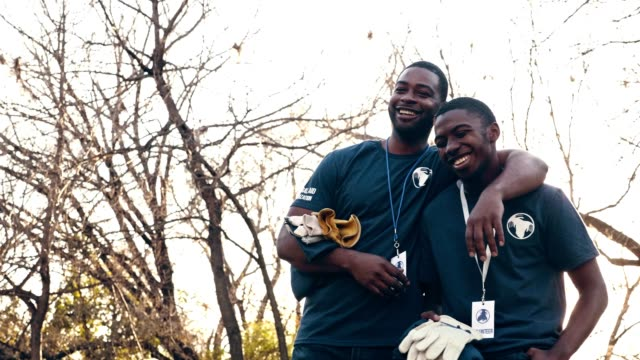 Cheerful mid adult man and his teenage son volunteer during community cleanup event