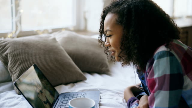 Cheerful mixed race girl having video chat with friends using laptop camera while lying on bed video
