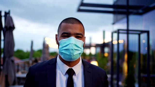 cheerful modern businessman wearing protective face mask during covid-19 pandemic - businessman covid mask video stock e b–roll