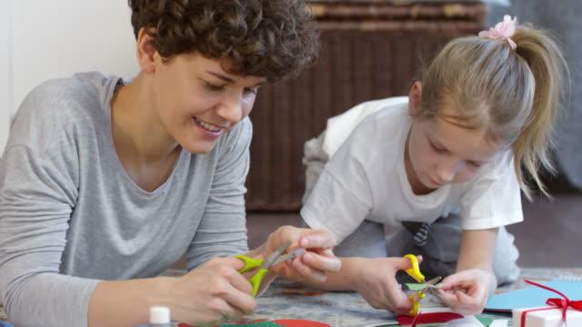 歡快的媽媽和女兒為耶誕節做紙裝飾 - 手工藝 個影片檔及 b 捲影像