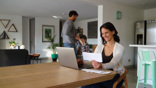 Cheerful mother working on laptop looking at her family at background play together all having fun