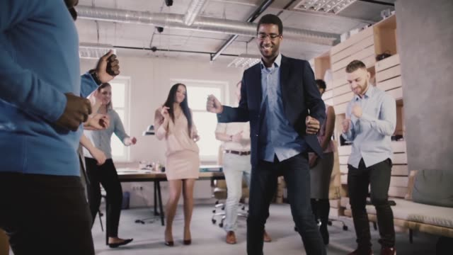 Gens d'affaires multiethnique joyeux danser ensemble au party de teambuilding de bureau en bonne santé, célébrer les succès de ralenti - Vidéo