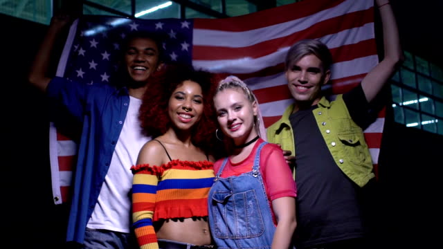 Cheerful multi-ethnic teenagers posing with flag of usa, patriotism, support