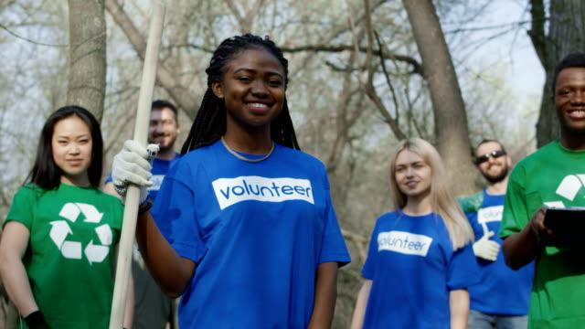 Cheerful multiethnic volunteers in forest