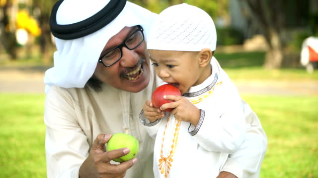 cheerful Muslim grandfather in traditional garments let son try to eat apple