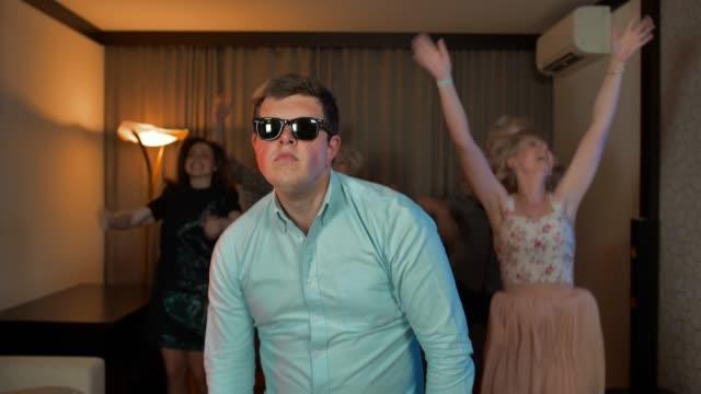 vídeos de stock, filmes e b-roll de macho de alegre nerd com óculos dançando e festejando - posição
