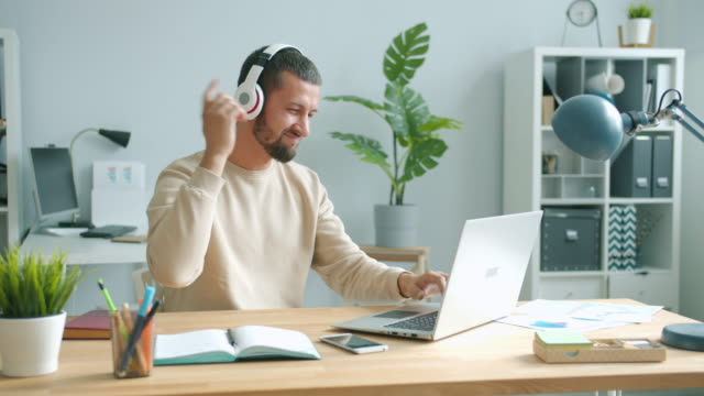 Cheerful office worker wearing headphones moving arms dancing and using laptop