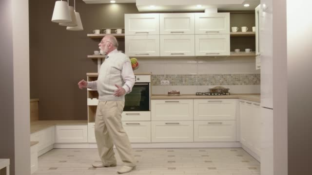 cheerful old man dancing in the kitchen - estatico video stock e b–roll