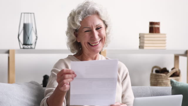 Cheerful old woman reads mail letter excited by good news Cheerful old senior woman reads postal mail approval letter excited by good news. Excited elder lady feels satisfied with bill or tax refund, bank service offer, holding paper sitting on sofa at home goal post stock videos & royalty-free footage