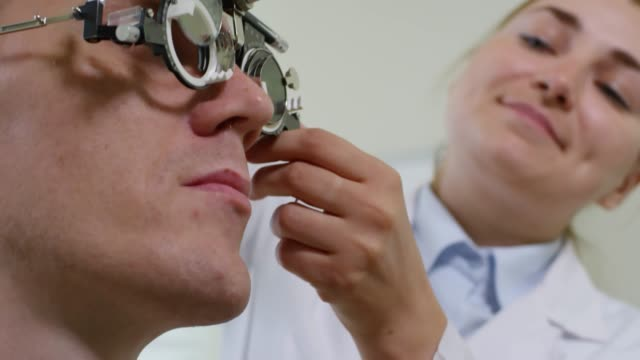 Cheerful Optometrist Checking Eyesight of Male Patient Low angle shot with rack focus of cheerful female optometrist changing lenses on trial frame worn by male patient during eye exam eye chart stock videos & royalty-free footage
