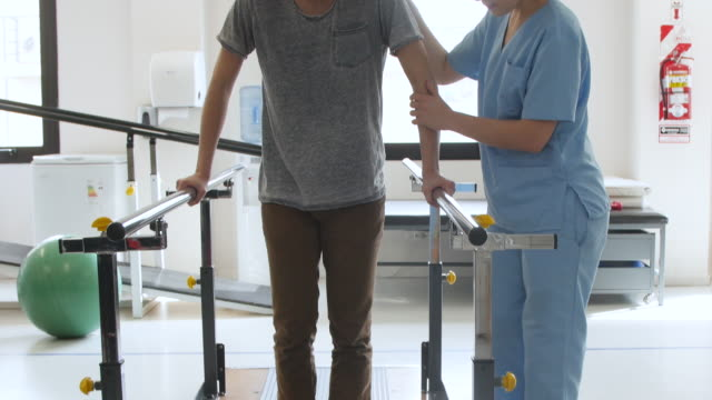 Cheerful patient smiling while walking with the help of parallel bars and therapist standing next to him Cheerful patient smiling while walking with the help of parallel bars and therapist standing next to him - Physical Therapy orthopedic equipment stock videos & royalty-free footage
