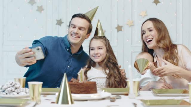 glada människor firar en års födelsedag i partyhatt tillsammans. - birthday celebration looking at phone children bildbanksvideor och videomaterial från bakom kulisserna