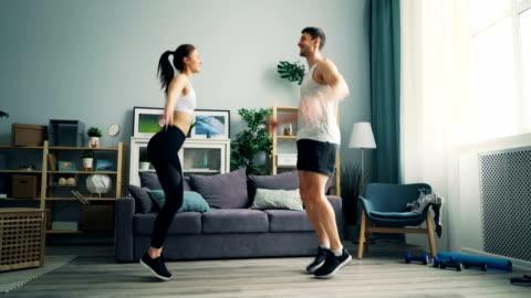 allegri coppia di persone in abbigliamento sportivo facendo sport saltando alzando le braccia a casa - allenamento video stock e b–roll