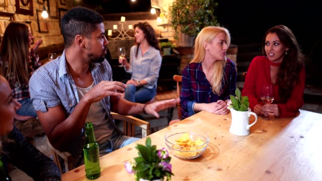 fröhliche menschen, die an einer bar sitzen und ihre zeit genießen - klatsch stock-videos und b-roll-filmmaterial
