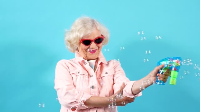 Cheerful positive grandmother having fun with bubbles