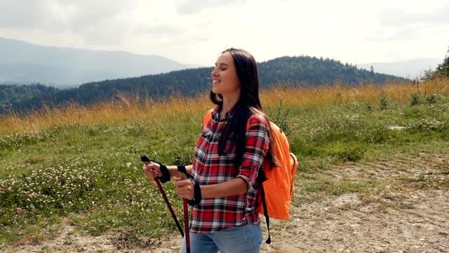 stockvideo's en b-roll-footage met vrolijke zwangere vrouw wandelen met stokken in bergen, slow-motion - sportartikelen