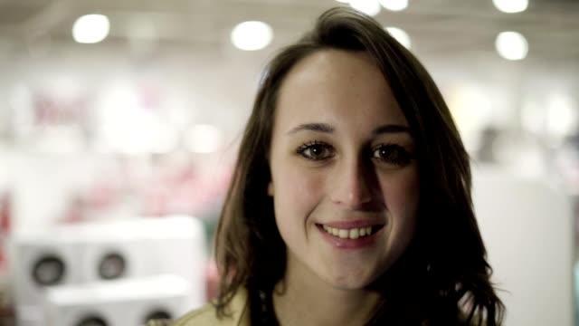 glad vacker ung latinsk kvinna i överrock stående i butik - endast en ung kvinna bildbanksvideor och videomaterial från bakom kulisserna