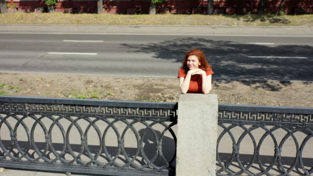 A cheerful red-haired athlete is waiting for the track to run