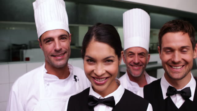 radosny restauracja pracowników uśmiecha się do kamery - uniform filmów i materiałów b-roll