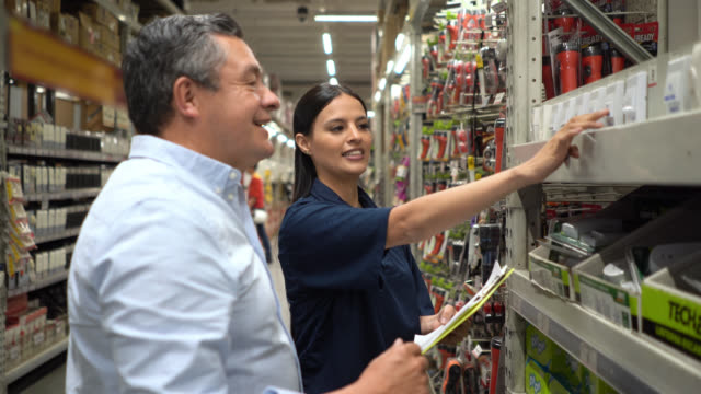 Cheerful saleswoman helping male customer at a hardware store Cheerful saleswoman helping male customer at a hardware store while holding a clipboard saleswoman stock videos & royalty-free footage