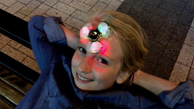 Cheerful school girl playing with a luminous fidget spinner, spins on the forehead, evening outdoors. A popular trendy toy. video