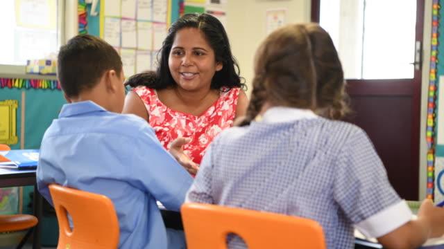 Cheerful school teacher talking to boy and girl in classroom video