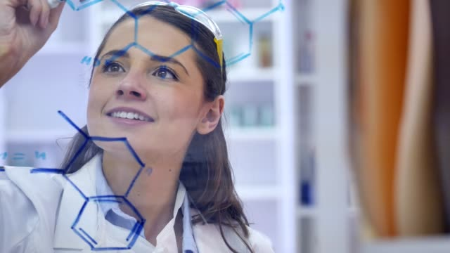Cheerful scientist smiles confidently while drawing molecular structure Confident young Caucasian female scientist smiles confidently while drawing molecular structure on transparent board. chemical formula stock videos & royalty-free footage