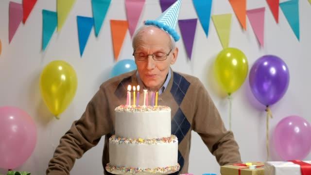 Senior gai soufflant des bougies sur un anniversaire gâteau et brandissant ses pouces - Vidéo