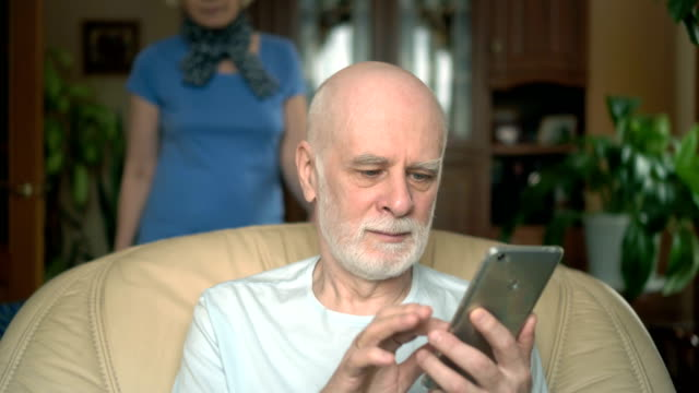 Cheerful senior couple at home. Husband using smartphone, browsing, reading. Wife comming hugging video