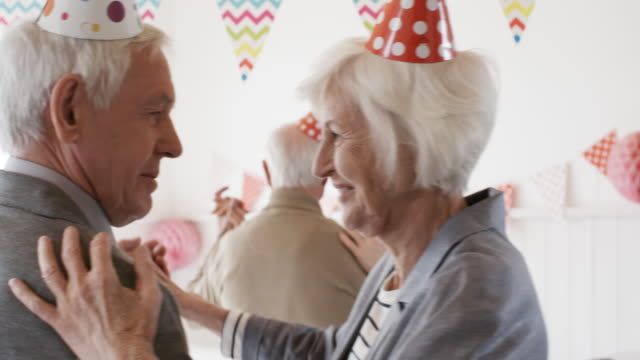 cheerful senior couple dancing at birthday party - happy holidays filmów i materiałów b-roll