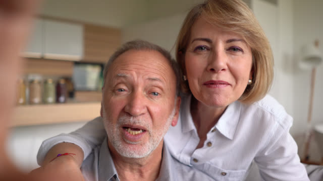 Cheerful senior couple on a video conference saying hello facing camera smiling video