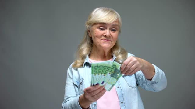 glada senior kvinna kastar eurosedlar, slösa pengar, låneservice - spendera pengar bildbanksvideor och videomaterial från bakom kulisserna