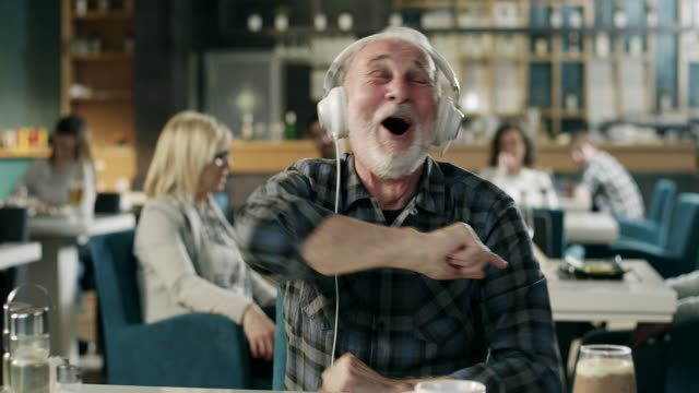 Cheerful senior man listening music on headphones in restaurant