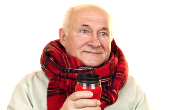 Cheerful senior man wearing a scarf holding thermos smiling happily video