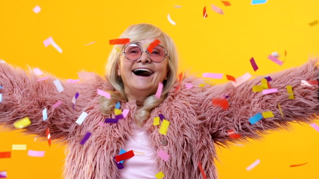 Cheerful senior woman stylish fur enjoying falling confetti, festival happiness