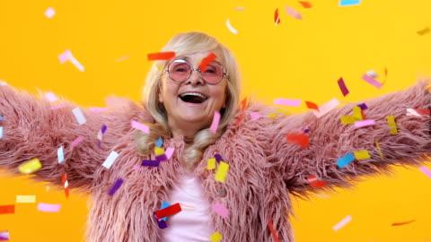 neşeli kadın kıdemli şık kürk zevk düşen konfeti, festival mutluluk - kutlama stok videoları ve detay görüntü çekimi