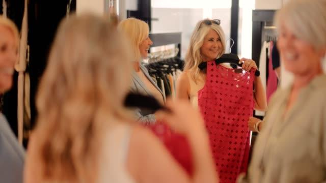 vídeos de stock, filmes e b-roll de alegres mulheres sênior se divertindo às compras em loja de roupas - boutique