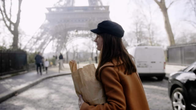Cheerful smiling Caucasian woman walking at Paris Eiffel Tower, giving a piece of French bread to operator slow motion. video
