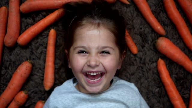 fröhlich lächelndes kind liegt zwischen karotten - karotte peace stock-videos und b-roll-filmmaterial