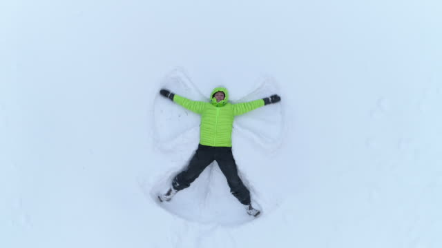 aerial cheerful smiling girl making snow angles in fresh snow on snowy mountain - angelo video stock e b–roll