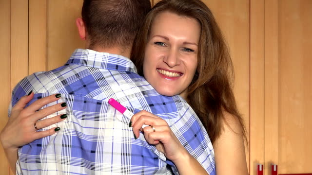 Cheerful smiling wife woman embrace her husband man with pregnancy test in hand video