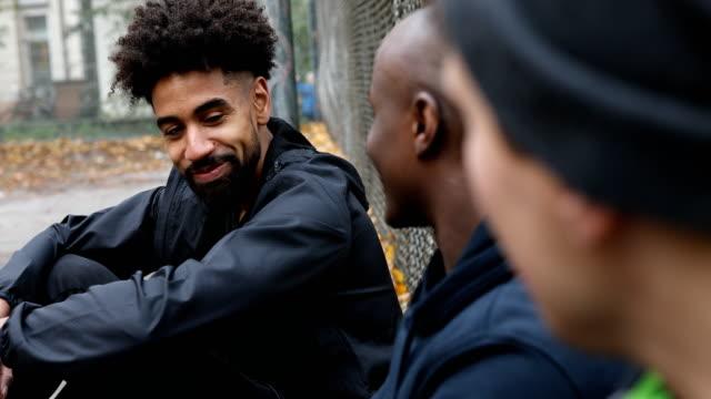 fröhlich fußballspieler diskutieren von zaun - freund stock-videos und b-roll-filmmaterial