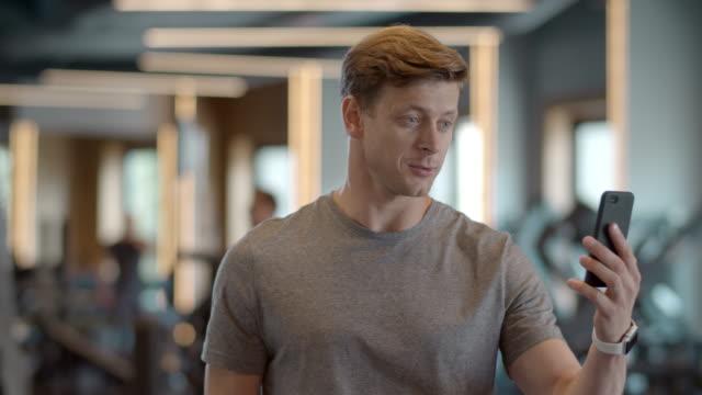 stockvideo's en b-roll-footage met vrolijke sportsman die hi in gymnastiek zegt. glimlachende atleetmens die videovraag heeft - call center