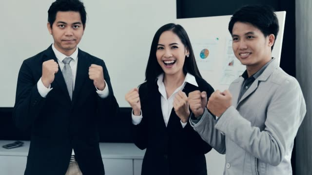 Cheerful successful group business people rejoycing with fists raised, achievement , slow motion video