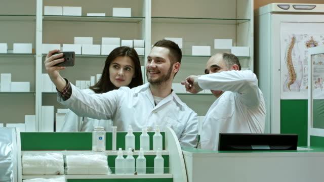 glada team av apotekare och praktikanter ta selfie via smartphone på arbetsplatsen - hospital studio bildbanksvideor och videomaterial från bakom kulisserna