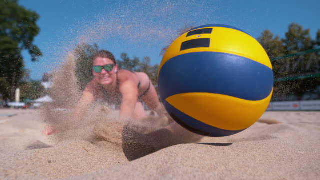 CLOSE UP: Cheerful teammates dive into the sand in effort to reach the ball. SLOW MOTION, CLOSE UP, DOF: Cheerful female teammates dive into the sand in effort to reach the ball during a beach volleyball tournament. Athletic women jump towards the ball and crash into the sand. beach volleyball stock videos & royalty-free footage