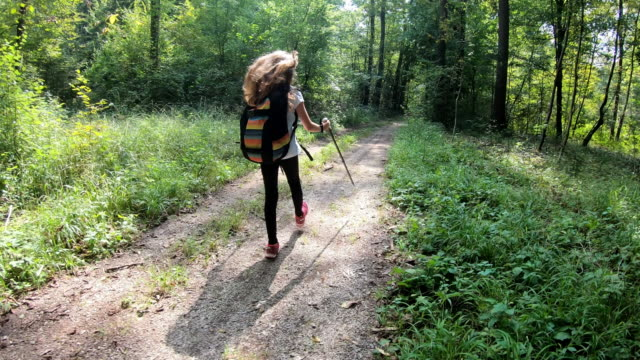 Cheerful teen girl jumping in forest with backpack