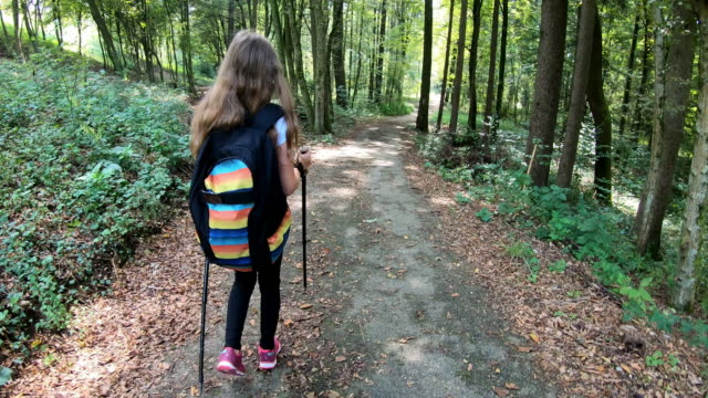Cheerful teen girl walking in forest with backpack