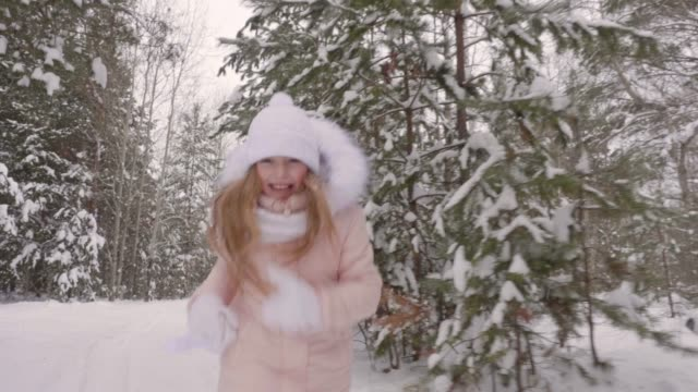 Cheerful teenager girl running in snowy park while winter walk slow motion